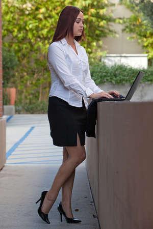high heels: Pretty twenties native american businesswoman working with laptop Stock Photo