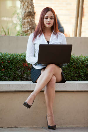 Pretty twenties native american businesswoman working with laptop photo
