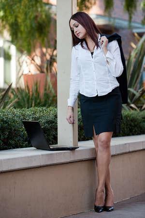 Pretty twenties native american businesswoman working with laptop photo