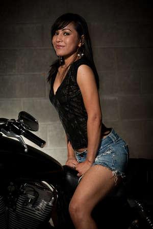 motorrad frau: Attraktive dreißiger Jahren asiatische Frau sitzt auf Motorrad Lizenzfreie Bilder