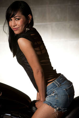 Attractive thirties asian woman sitting on motorcycle photo