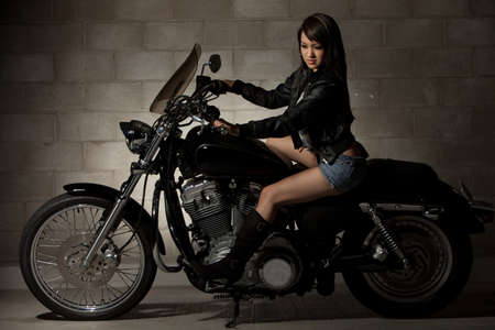 Sexy attractive twenties asian woman sitting on motorcycle