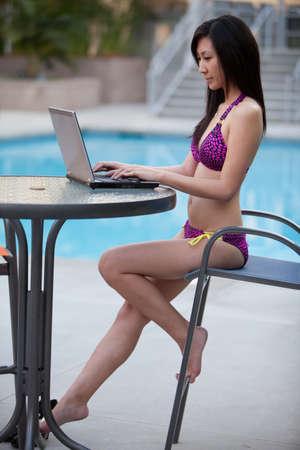수영장에서 노트북에 근무하는 아시아 여자 스톡 콘텐츠