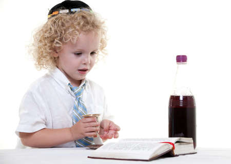 Cute young blond toddler jewish boy playing pretend photo