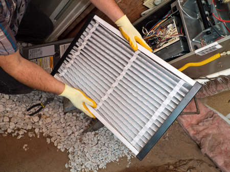 furnace: Hispanic airconditioning repair man performing maintenance