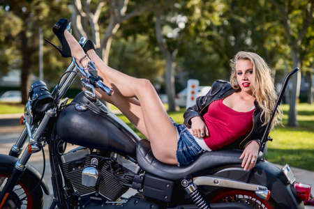 Sexy caucasian blond woman on motorcycle Фото со стока