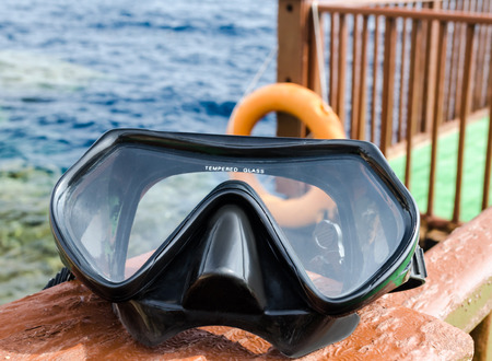 Safe swimming illustration mask for scuba diving lies on a wooden