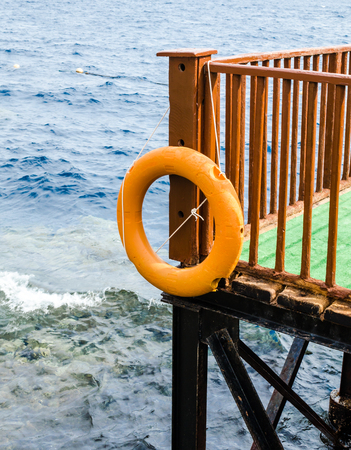 orange lifebuoy hanging on a brown wooden pier against the blue