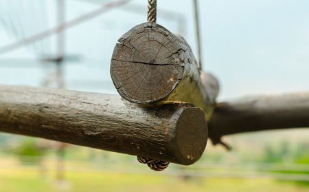 small wooden logs of a suspended rope road close-up against a blue sky
