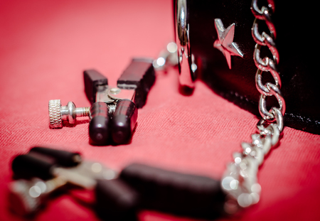 bdsm accessory human collar and accessory nipple clasp with metal chain on a red background close-up 版權商用圖片