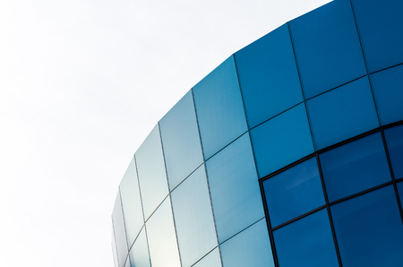 facade of an office building with blue walls and mirrored windows