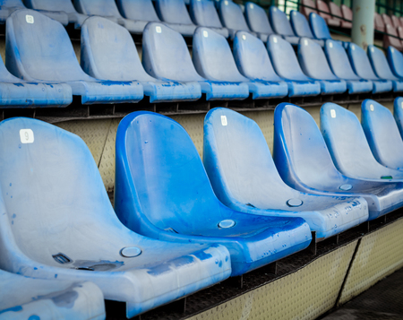 emphasis on one unlike chair among the rows of seats in the empty stands of the stadium Stock fotó