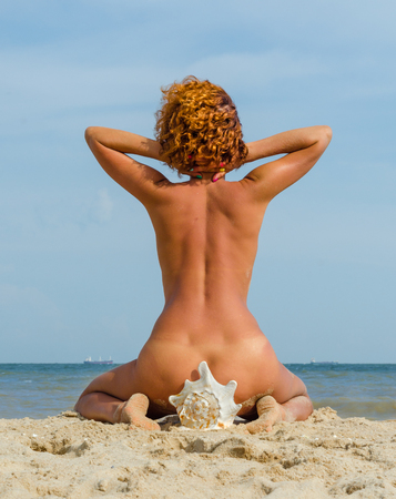 young red-haired  tanned woman sitting on a big seashell by the sea