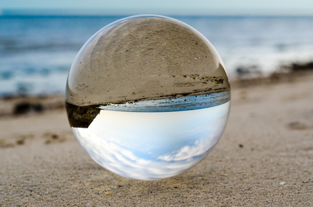 glass crystal ball lens lies on the sand of the sea shore