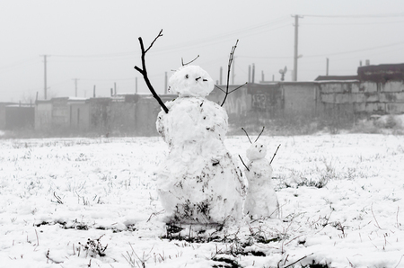 two creepy snowmen from dirty snow on the background of concrete walls and pipes Stock Photo