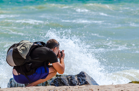young man squatting photographs the surf and rocks on sea