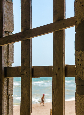 view of the seashore with running child through the boarded up Imagens - 116285118