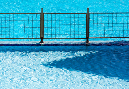 metal fence grill in the pool with blue water Banque d'images