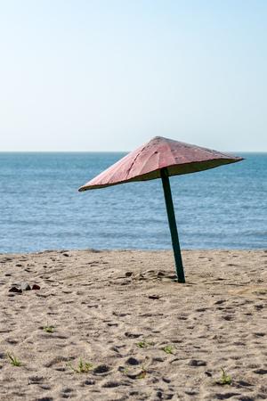 old rickety shabby beach umbrella by the sea