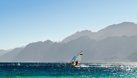 two windsurfers ride on the background of high rocky mountains in Egypt Dahab