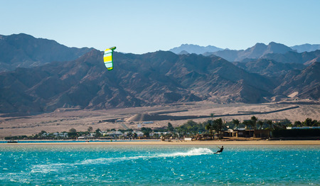 kitesurfer rides in the Red Sea on the background of a rocky coast in Egypt Dahab Stock Photo