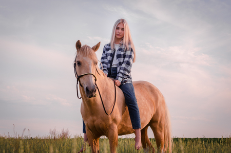 young blonde girl dressed in blue jeans and a plaid shirt sits on a horse at the ranch closeup