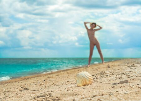 young nude girl with a hat walks on an empty beach near the sea surf against the blue sky with clouds in summer