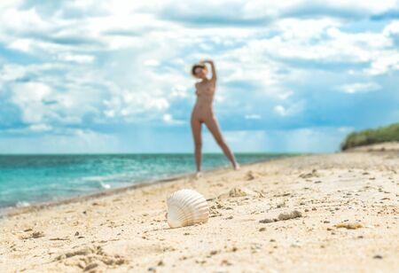 jeune fille avec un chapeau marche sur une plage vide près de la mer surf contre le ciel bleu avec des nuages en été