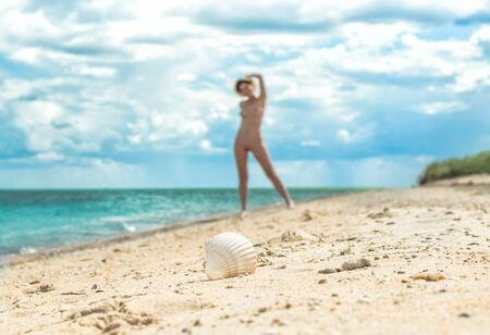 young girl with a hat walks on an empty beach near the sea surf against the blue sky with clouds in summer