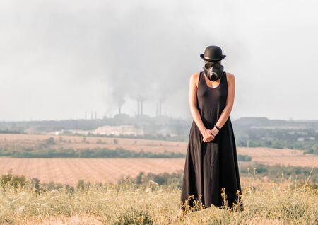 young girl in a black dress and gas mask on the background of smoking factory chimneys Stock Photo
