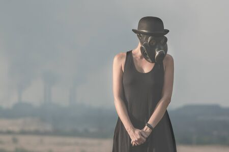young girl in a black dress and gas mask on the background of smoking factory chimneys close up