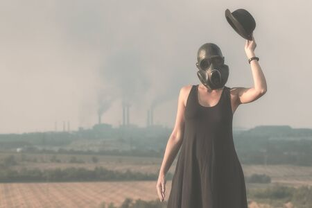 young girl in a black dress and gas mask on the background of smoking factory chimneys in Ukraine