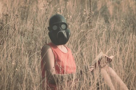 young woman in gas mask in a red dress with a book in her hands sits in the dry grass