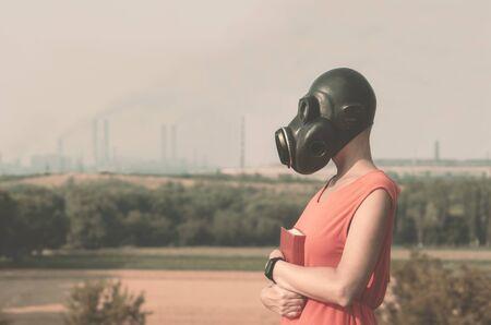 giovane ragazza in una maschera antigas in un vestito rosso con un libro in mano sullo sfondo di ciminiere fumanti