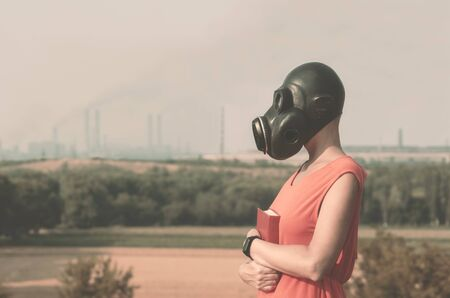 young girl in a gas mask in a red dress with a book in her hands against the background of smoking factory chimneys 免版税图像