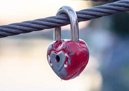 red peeling wedding lock on a rope with a key hole Imagens