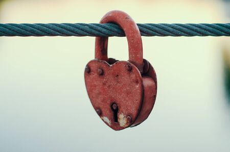 red peeling wedding lock on a rope with a key hole Banque d'images