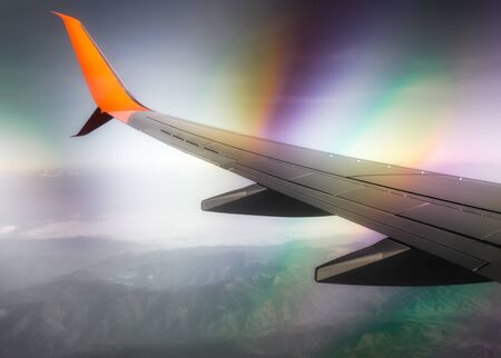 wing of a civilian airliner in flight above clouds and mountains with color optical effect Stok Fotoğraf