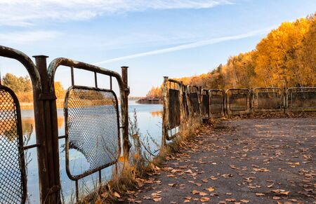 autumn landscape river and pier with an iron fence with a sunken destroyed house in Chernobyl in Ukraine Stok Fotoğraf