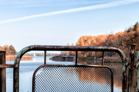 autumn landscape river and iron fence with a sunken destroyed house in Chernobyl