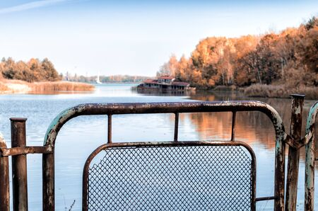 autumn landscape river and iron fence with a sunken destroyed house in Chernobyl in Ukraine Stok Fotoğraf
