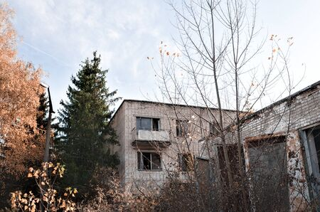 old abandoned brick house with a balcony and trees with a lamppost in Chernobyl Ukraine in autumn Stock Photo