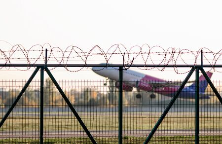 flying airliner airplane and a fence with barbed wire and plants and trees