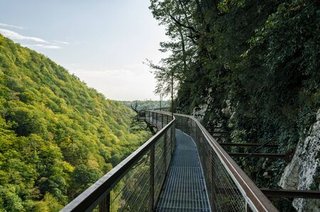 landscape of a long safe tourist metal bridge in Okatse canyon in Georgia in autumn against the backdrop of mountains and forest and sky with clouds