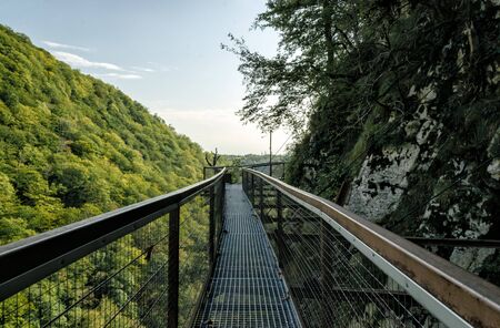 long safe tourist metal bridge in Okatse canyon in Georgia in autumn against mountains and forest and sky with clouds