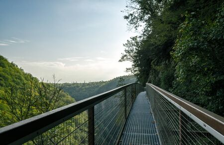long safe tourist metal bridge in a canyon in Georgia in the fall against the backdrop of mountains and forest and sky with clouds Reklamní fotografie