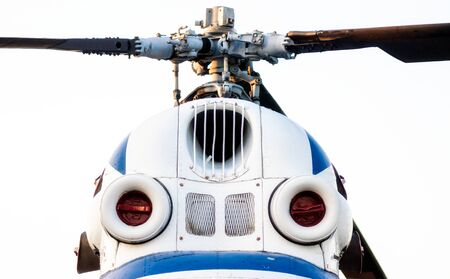 cockpit of an old white helicopter with propeller blades isolated close up