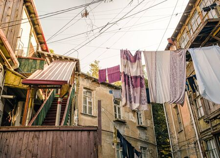 old houses with stairs and balconies with ropes and clothes in Tbilisi Georgia