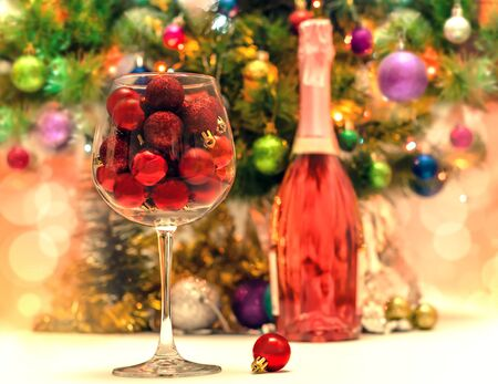 red glitter balls in a large wine glass against the background of a decorated Christmas tree