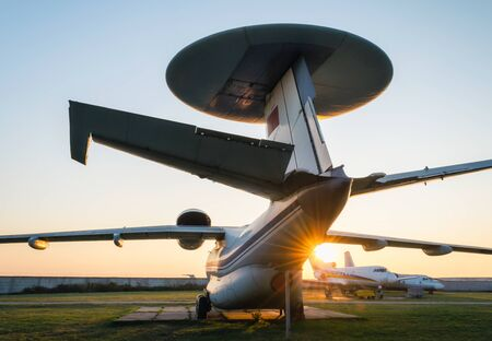 old soviet reconnaissance aircraft at the airport with the rays of the evening sun